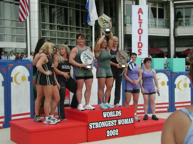The strongest woman in the world, Jill Mills, proudly holds her award at the podium after winning the 2002 World's Strongest Woman Award.